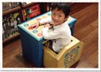 青いジュニアデスクチェアに座りデスクの上に腕を置き、笑顔でこちらを振り返り見上げている男の子の写真