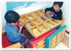 ジュニアデスクチェアを向い合せに二つ並べ、天板の蓋を取って中にたくさんおもちゃを入れて遊んでいる二人の男の子の写真