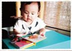 ベビーデスクの上に絵本を開いて眺めている赤ちゃんの写真