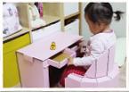 ベビーチェアに座り、デスクの引き出しを開けて中を見ている小さい子供の写真