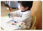 ベビーチェアに座り、ベビーデスクの上のスケッチブックにクレヨンでお絵かきをしている小さい子どもの写真