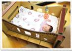 ダンボールゆりかごの布団のなかでぐっすり眠っている赤ちゃんの写真